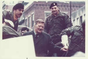 John Wayne, Joe Toplyn, and U.S. Army servicemen ride into Harvard Square on an armored personnel carrier on January 15, 1974.