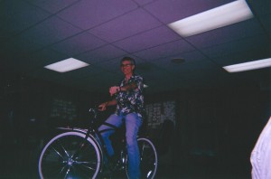 "Joe Toplyn riding a bike through the office of the TV show ""Monk"""